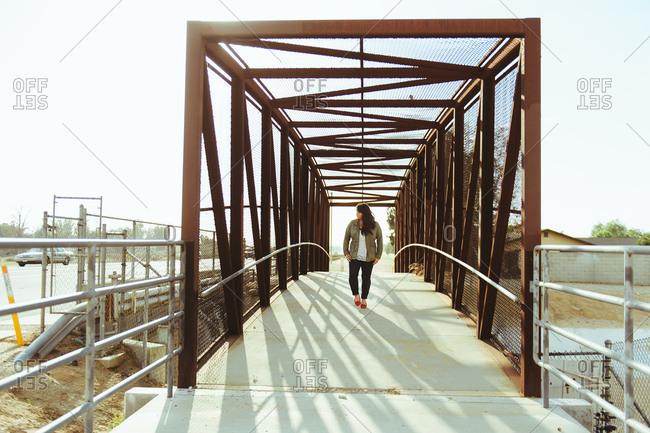 Woman walking over a bridge