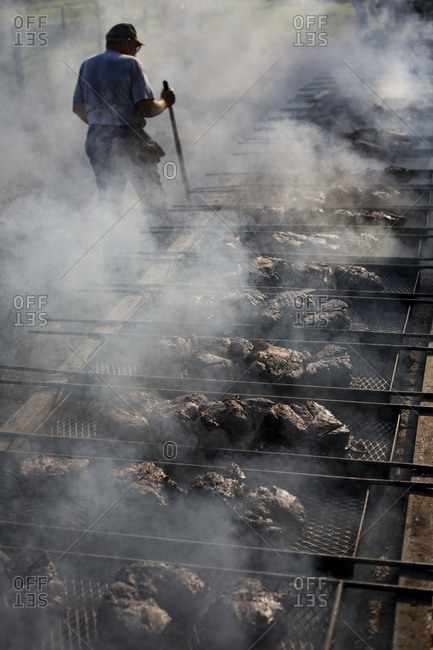 Person preserving meat by smoke