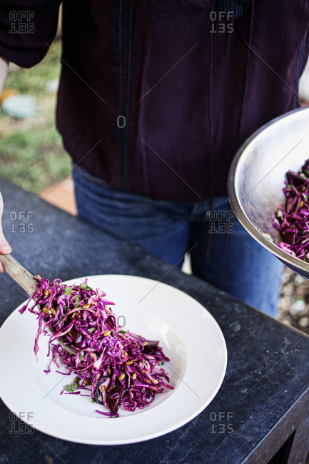 Person serving fresh ruby salad