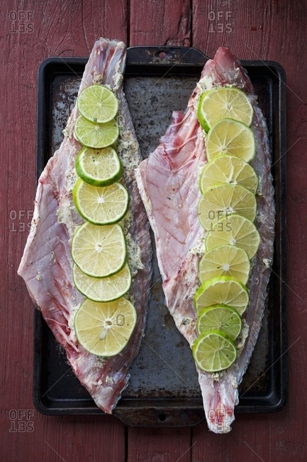Raw fish fillets with herb butter and lime slices