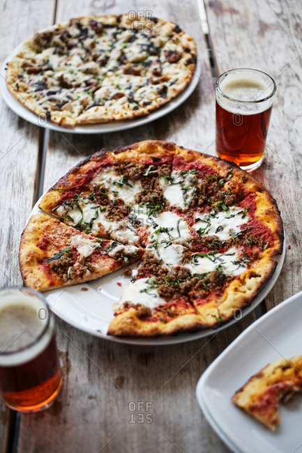 Two pizzas with glasses of beer