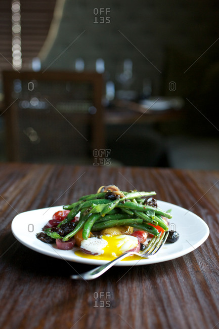 Green bean nicoise served with poached egg