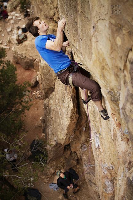 A man climbs up a rock face