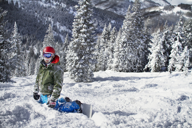 A snowboarder kneeling in the snow