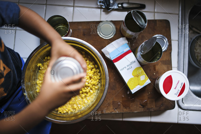 Young boy filling bowl with corn for corn bread