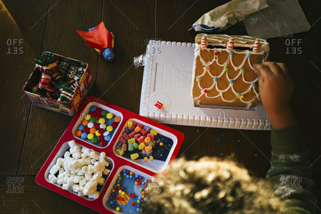 Young boy decorating gingerbread house