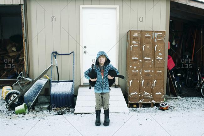Kid in hoodie holding ducks in winter