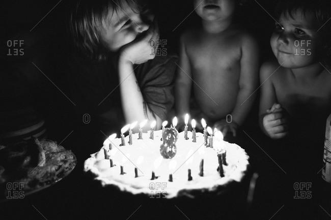 Three kids standing over a birthday cake