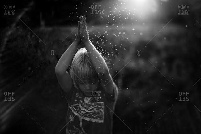 Boy spreading seedlets in black in white
