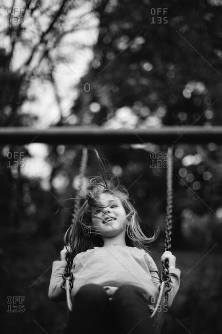 Girl swinging on swingset in yard