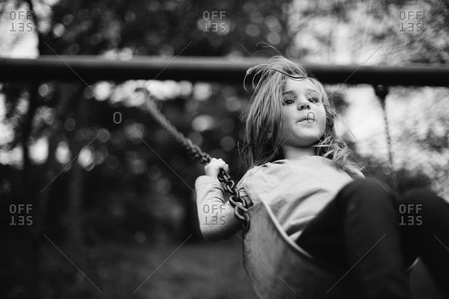 Young girl playing on swingset