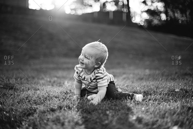 Toddler sitting in sunny yard