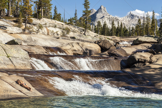 Young woman sunning on the rocks next to Tuolumne River in Yosemite National Park