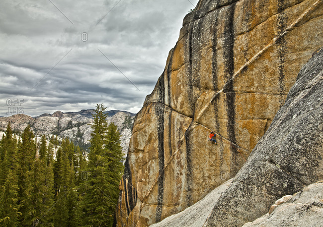 A climber dangles from the edge of a challenging cliff in Yosemite National Park