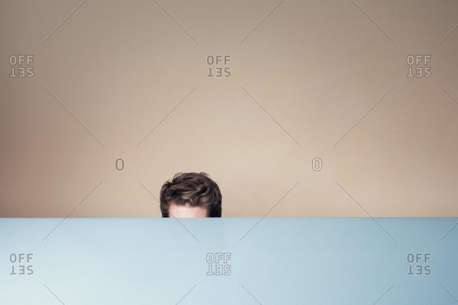 Man hiding behind a table