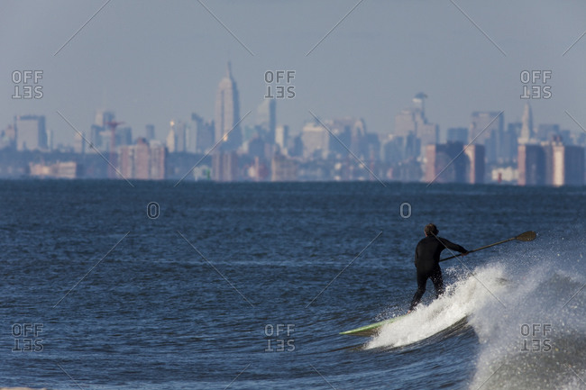 Paddle boarder surfing in waters off Manhattan