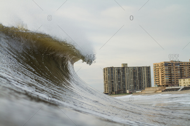 Wave curling near beach with hotels