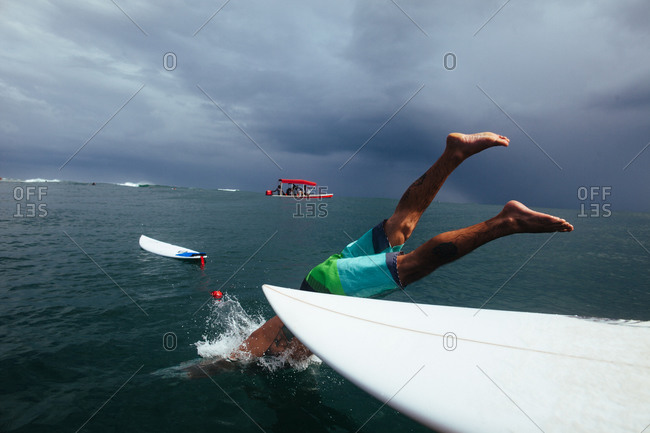Man diving off surfboard into dark sea