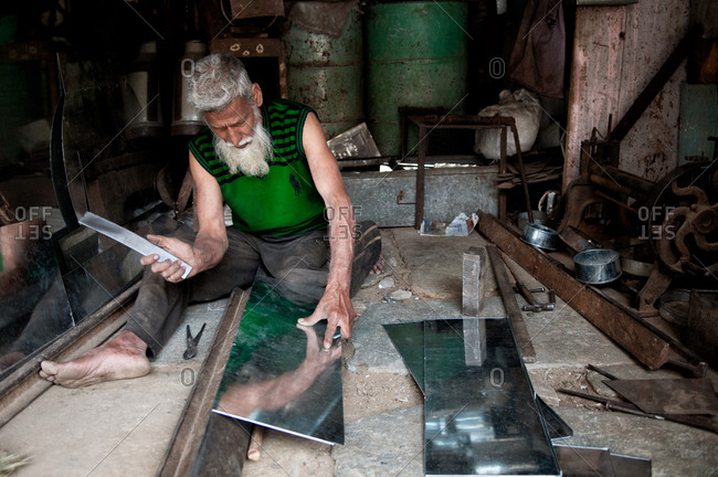 Udaipur, Rajasthan, India - March 3, 2014: An metalworker with aluminum sheets in India