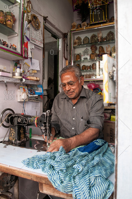 Delhi, India - March 3, 2014: Indian man sewing in his workshop