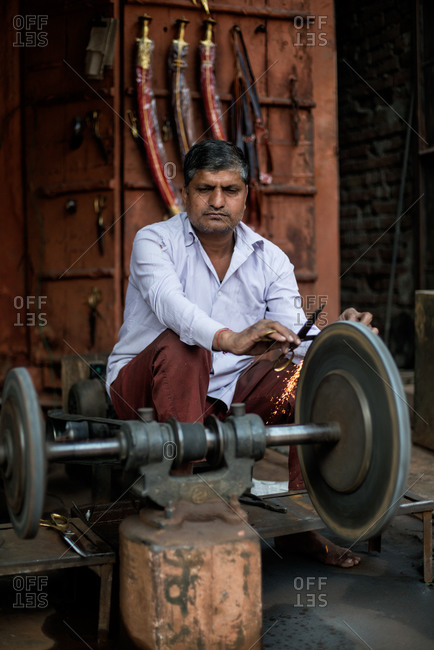 Delhi, India - February 26, 2014: A knife grinder working in Delhi, India