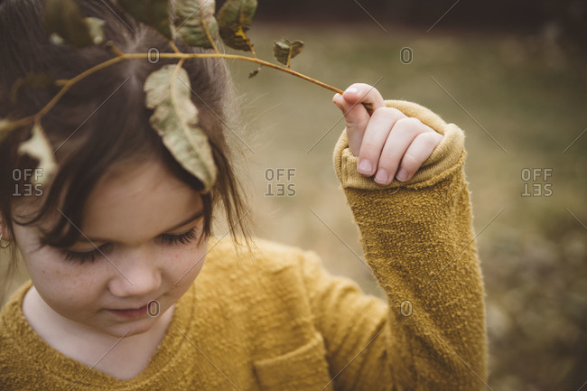 Young girl playing with a leafy twig