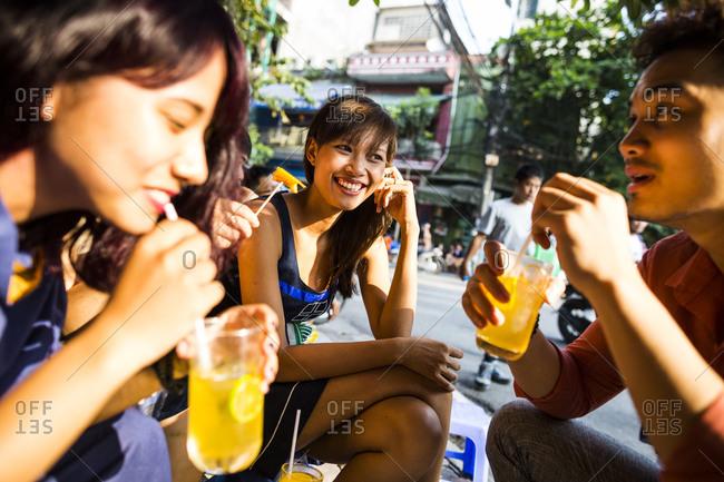 Hanoi, Vietnam - October 10, 2014: A group of friends drink tea and eat street snacks in the Old Quarter of Hanoi, Vietnam