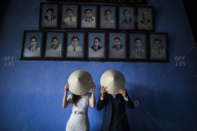 Hoi An, Vietnam - December 28, 2014: Young married couple hide behind conical hats