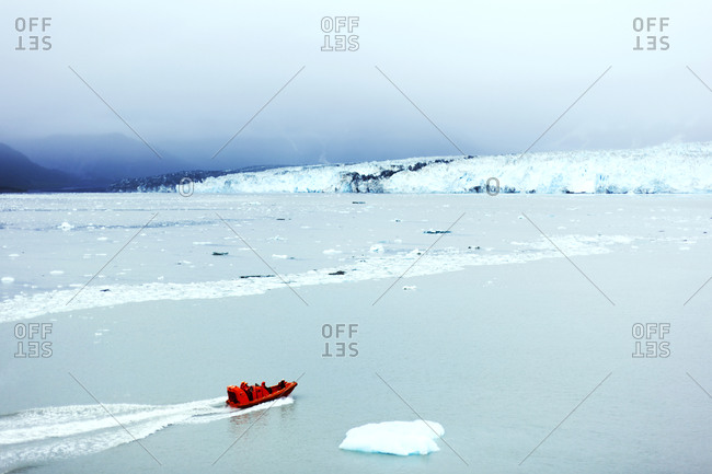 Red dinghy amidst glaciers in alaska