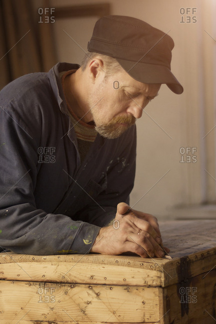 Carpenter carving into a wooden chest