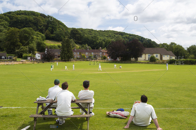 Players watching cricket match from picnic table