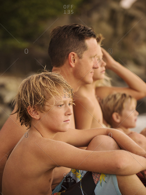 Family with three children  sitting on beach