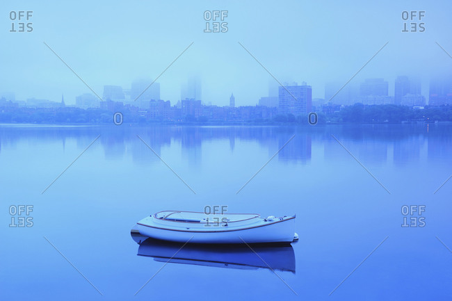 Lone boat on Charles river on foggy morning