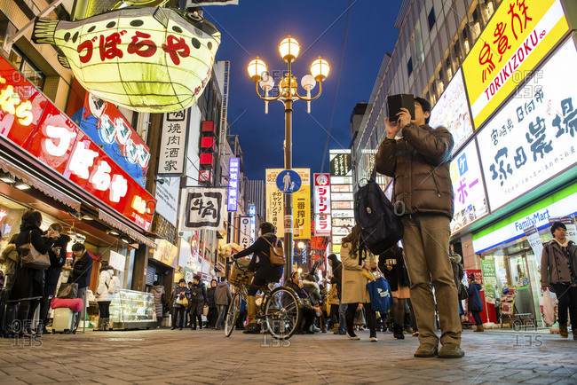 Osaka, Japan - December 31, 2014: Man taking a picture with his smartphone in Shinsaibashi