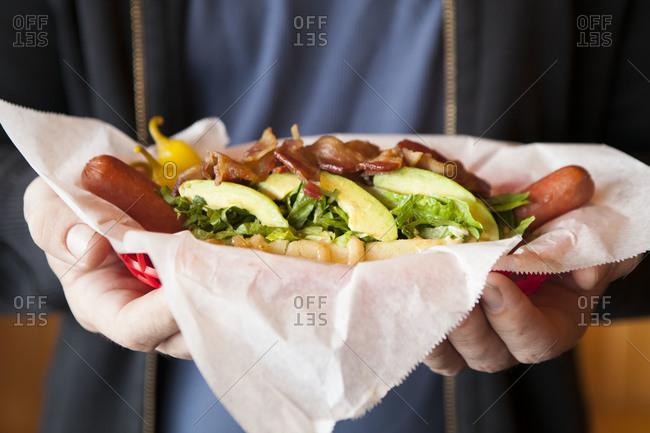 Oversized hot dog with bacon and avocado