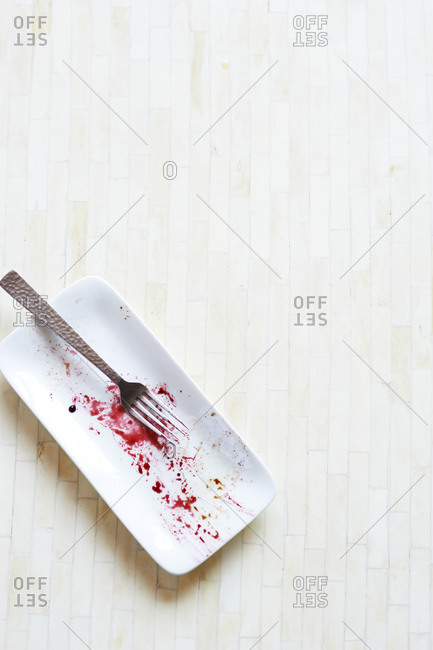 An empty salad plate with some beet juice residue
