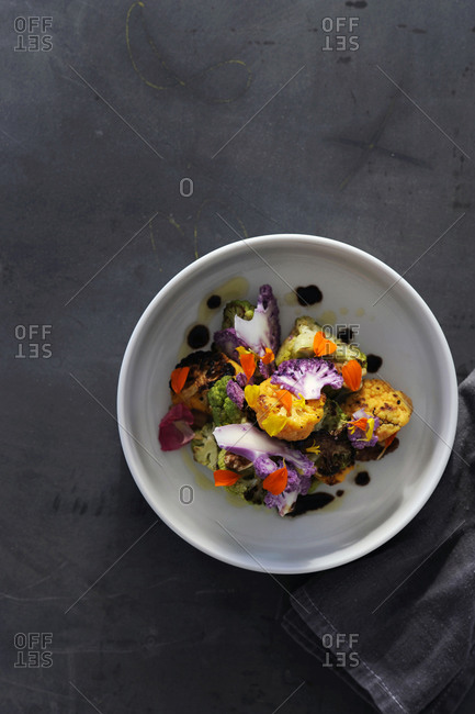 Cooked cauliflower, with fines herbs and edible flowers on balsamic vinegar sauce