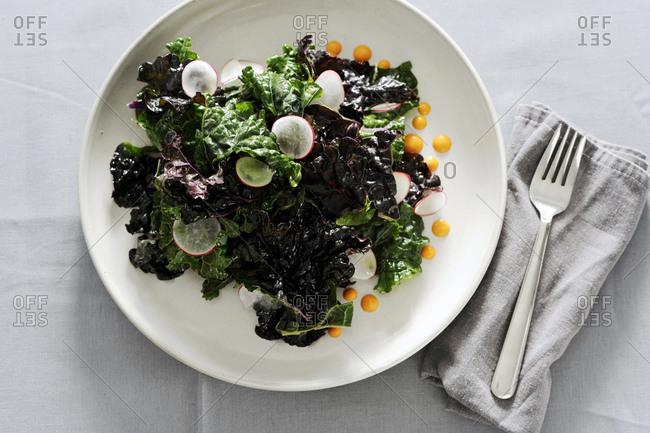 Kale salad with radish with harissa dressing