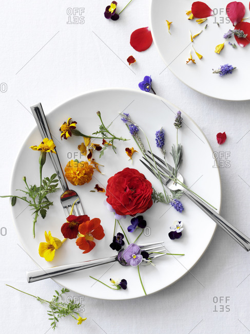 Various edible flowers  arranged on dish with forks