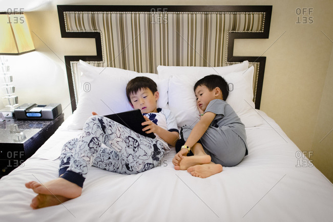 Boys watching tablet computer on hotel bed