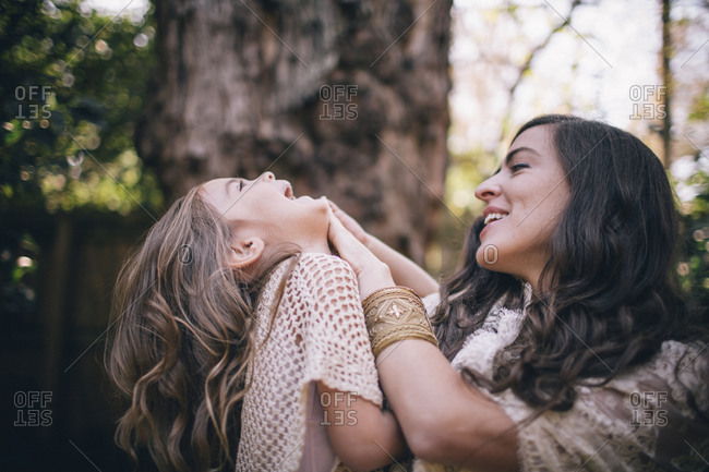 Woman and girl playing and laughing outdoors