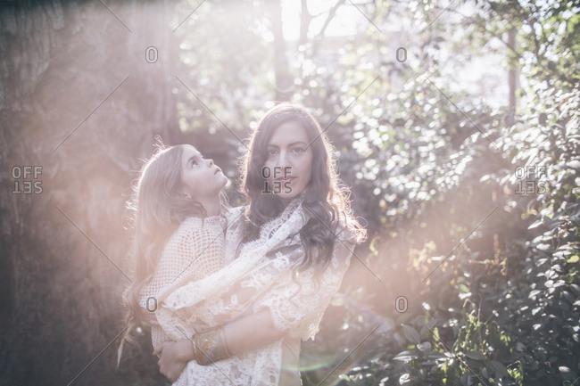 Woman holding girl in sun dappled woods