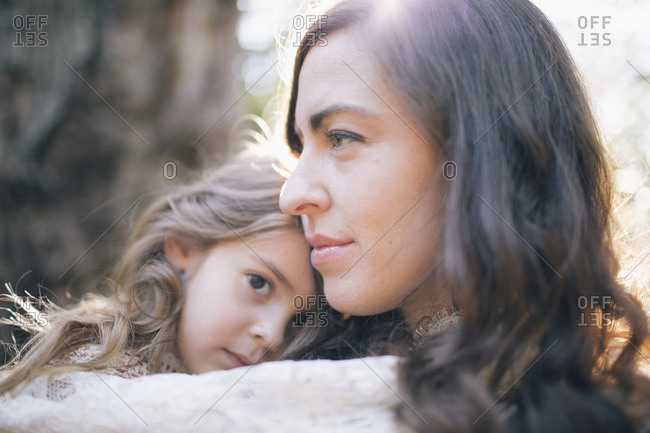 Mother and daughter embracing in woods