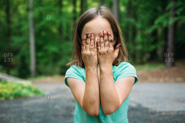 Young girl covering her face