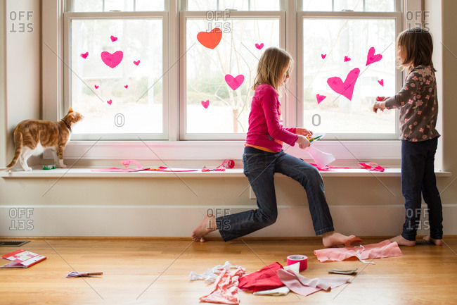 Young girls decorating the window for Valentine's day