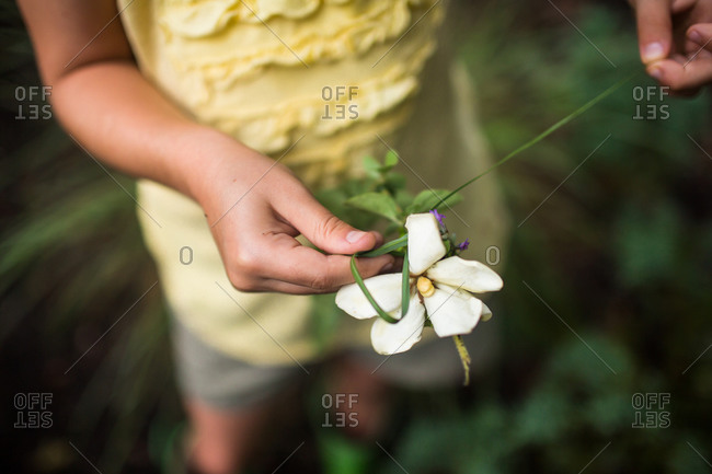 Young girl holding a white flower