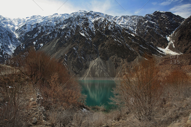 Majestic mountains reflected in brilliant green-blue glacial water in Pakistan