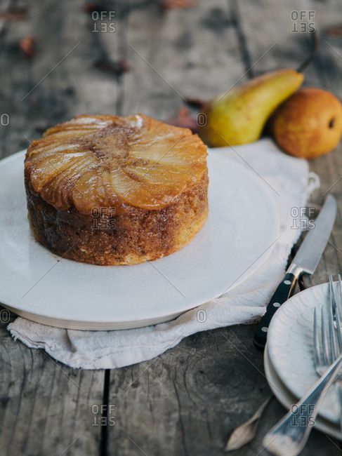Pear and Earl Gray Upside Down Cake on wooden table with pears