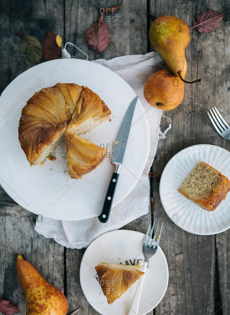 Overhead view of pear cake slices being served on wooden table