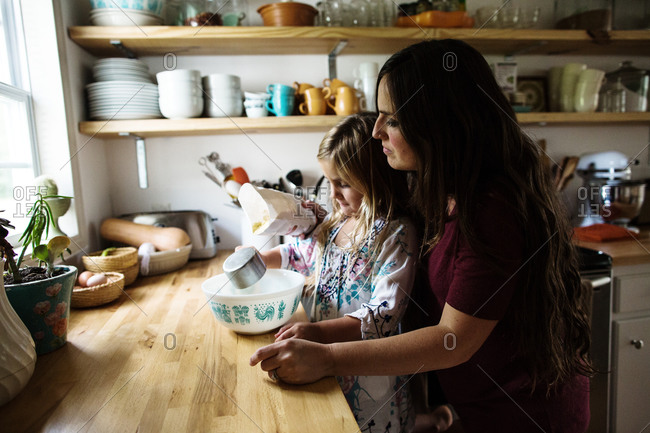 Mother helping daughter pour ingredients into bowl